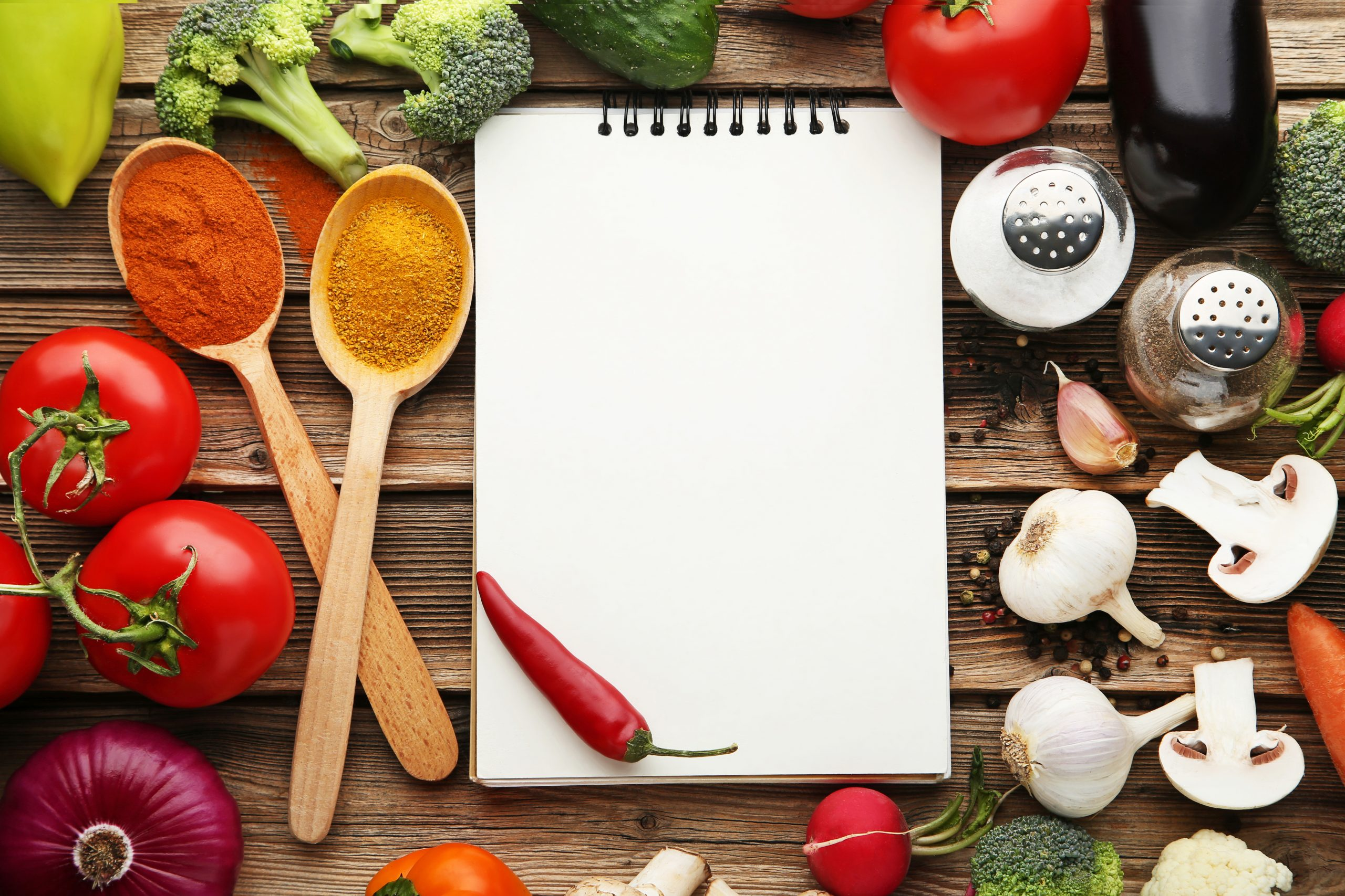 Blank recipe book with vegetables on wooden table