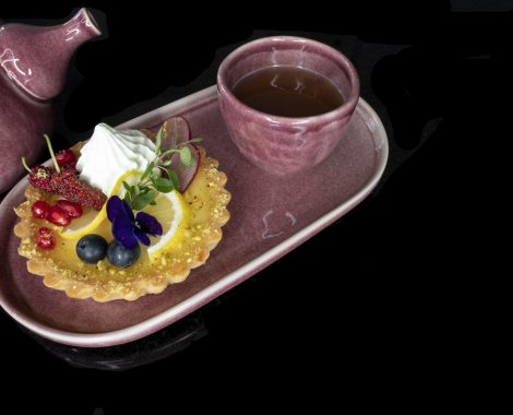 A piece of mixed fruit lemon tart on a purple ceramic plate with a tea cup and a chinese style ceramic tea pot. Black background.
